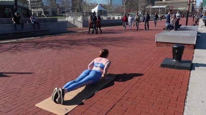 Девушка в нарисованной одежде занимается йогой на улице Балтимора