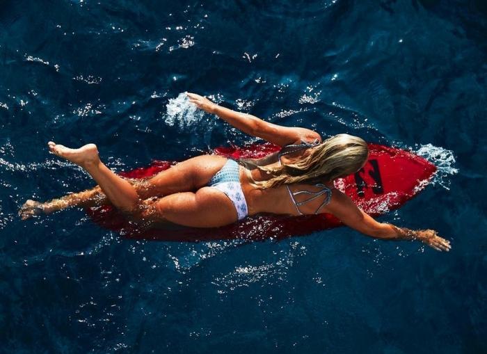Молодая серфингистка покоряет волны голышом